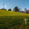 white cross on a grassy hill
