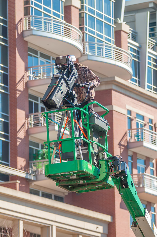 tv camera man recording event in a city on a lift