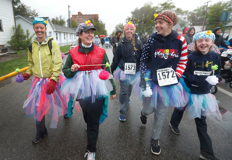 A family walks in the two mile race during the annual Montana Women's Run in Billings, Mont. on May 12, 2018. Calling themselves the 'Bathtub Beauties', the family made light of the soggy weather for the event.