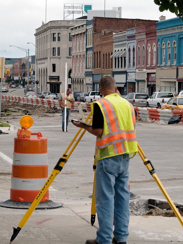 Surveyor at work plotting the construction on Mility Street.