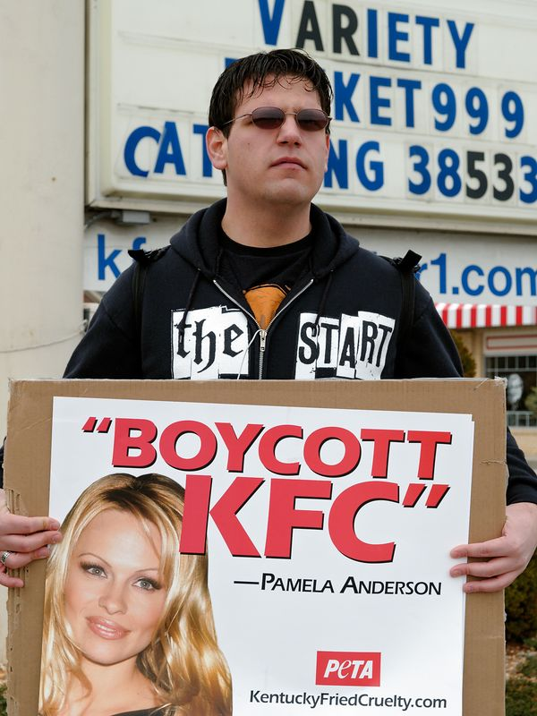 Two young men protest outside the Kentucky Fried Chicken on behalf of PETA, People for the Ethical Treatment of Animals.