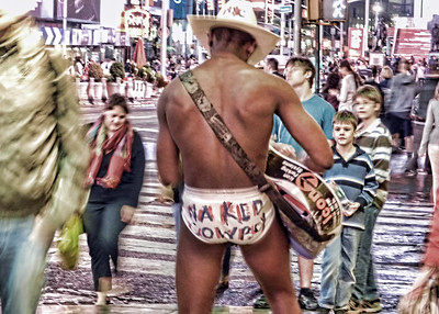July, 2013  The Naked Cowboy playing to the street crowds in New York City.