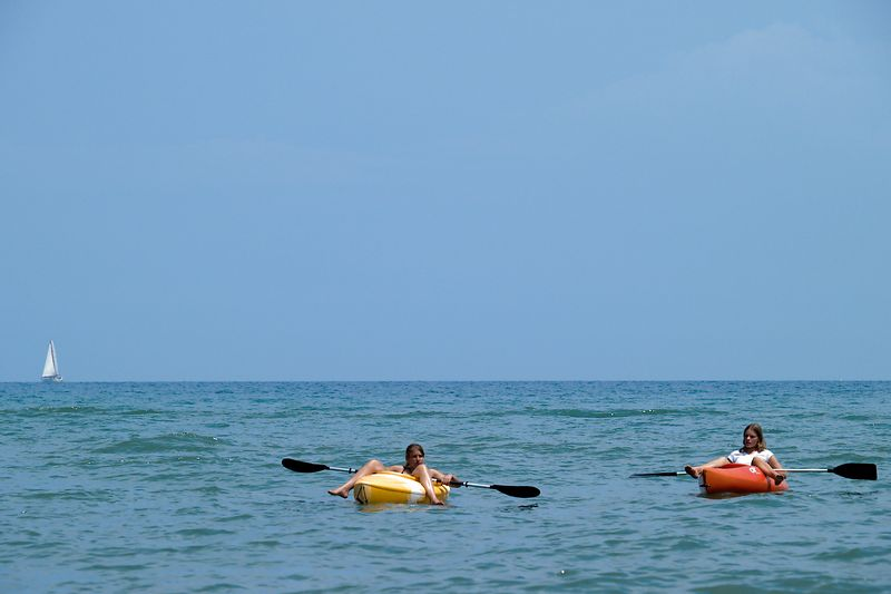 Two youths in kyaks relax in Lake Huron
