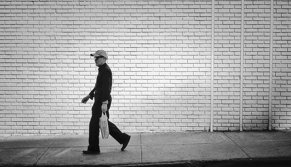 Gentleman walks past a white brick wall