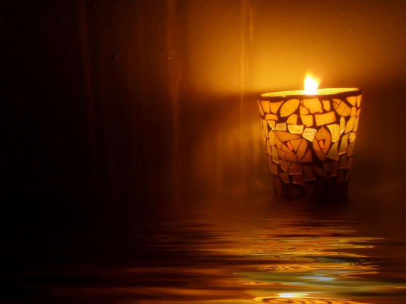 A lit candle reflected in rippled water.