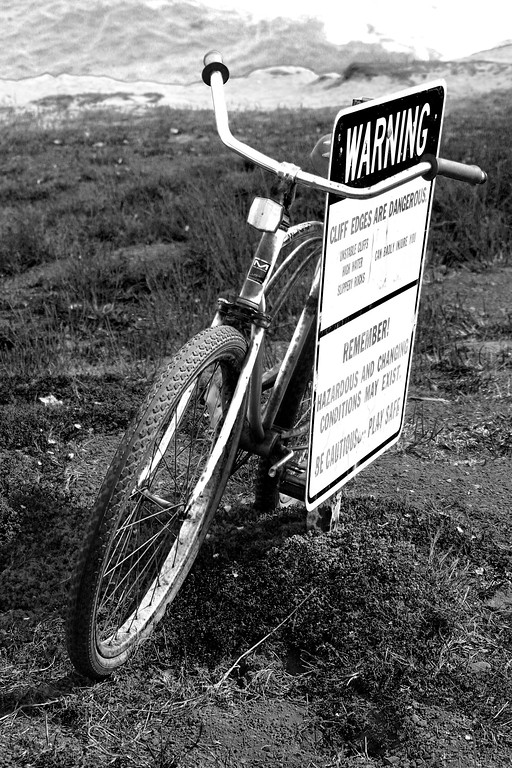 "Cruizer bike leaning against a ""Warning"" sign at Lighthouse Point in Santa Cruz California - © Simpson Brothers Photography"