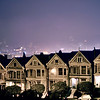 The Painted Ladies at night with downtown in the background in San Francisco California - © Simpson Brothers Photography