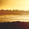 Surfer walking on the beach at sunset in Pacific Grove California - © Simpson Brothers Photography
