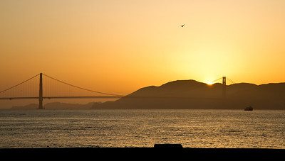 Golden Gate Bridge with the sun setting behind the Marin Headlands.