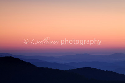 The sun rises into a cloudless sky above the Blue Ridge Mountains, as seen from Shenandoah National Park.