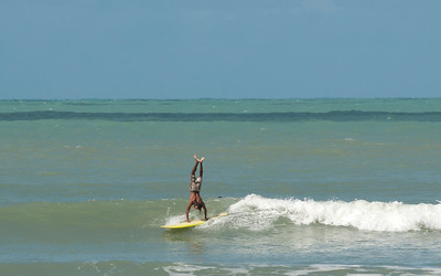 A man doing a hand stand on a longboard, Praia do Pipa, Rio Grande du Norte, Brazil.