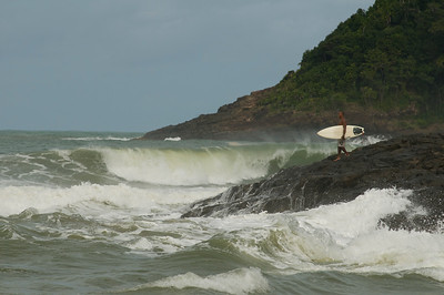 A Brasilian local stands on a rocky point looking at the surf in Itacare, Bahia, Brazil.