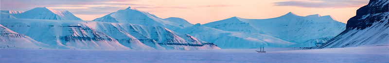 """Panorama from Tempelfjord, Svalbard, Norway. The sailboat """"Norderlicht"""" is frozen in the sea ice."""