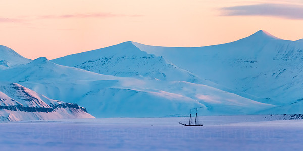 "Panorama from Tempelfjord, Svalbard, Norway. The sailboat ""Norderlicht"" is frozen in the sea ice."