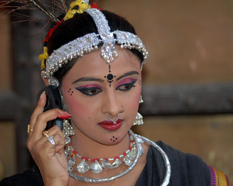 This lady who was part of the troupe from Orissa talking on the cellphone before their performance of song and dance at the Rajasthan Day Celebrations in Jaipur, March/April 2007, India.<br /> <br /> With the aim of showcasing Rajasthan State's culture & heritage and reviving the traditional sports, cuisines and folk-art, Rajasthan Diwas Celebrations were held from 21st March to 30th March 2007. Craft-Bazaar, Food Festival, Night Bazaar, Sports competitions, spectacular fire-works, Mega Cultural Concerts, and competitions for school students were organized.