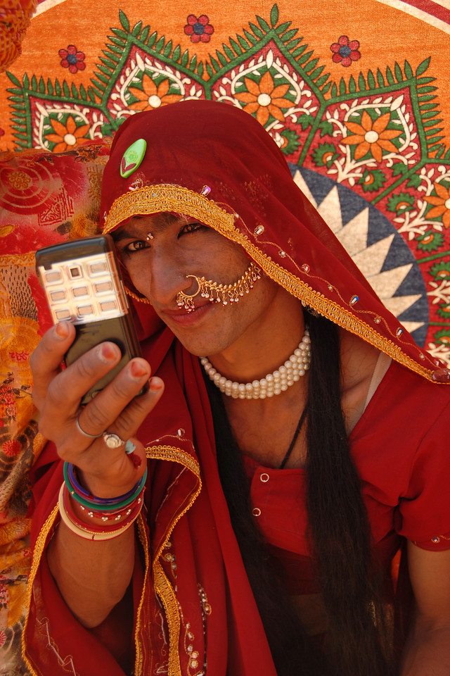 Part of the culture is to have only men dance. So one of the man dresses up as a lady. Seen here he is busy making calls on his mobile phone after the performance. <br /> <br /> Holi the Festival of Colours being celebrated in Jaipur, the Capital city of Rajasthan, India.