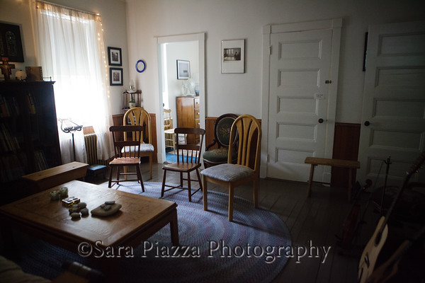 The living room - still set up from a recent song session. The door to a small single room is on the left, the door to the front hall is in the middle, and the door on the right leads to the gallery.