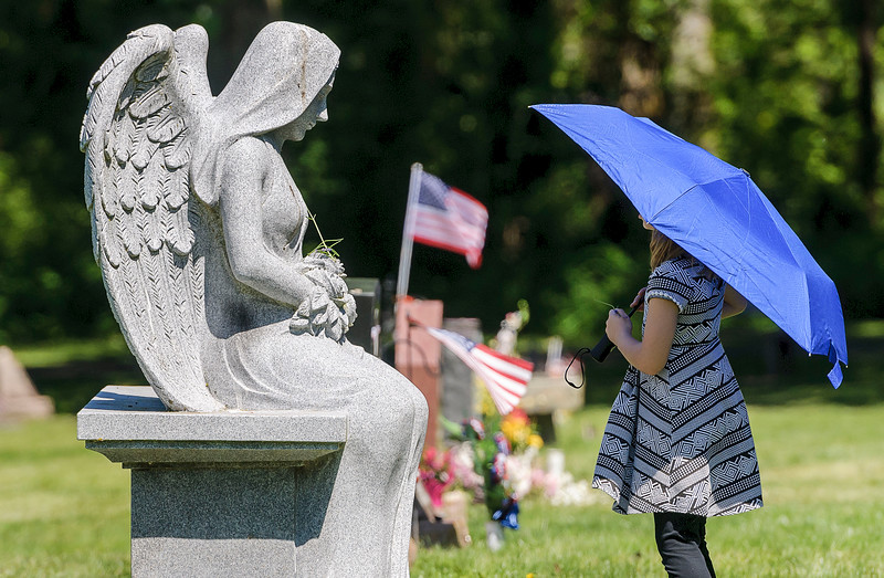 Jenna Clift, 7, pauses in front of an angel statue while placing flowers on graves after the conclusion of the Memorial Day service at the Veteran's Memorial on Monday afternoon May 30, 2016, at Bayview Cemetery in Bellingham, Wash. (© Paul Conrad/Paul Conrad Photography
