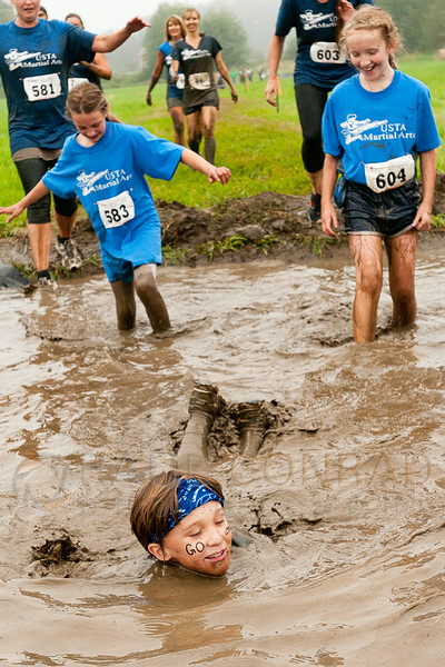 © Paul Conrad/The Bellingham Herald - Ty Warner, 9, of Ferndale, Wash., leads his team , USTA Martial Arts, out of the Holee Kow (cq) mud pit during the 3rd annual Mud to Suds race on Saturday morning August 16, 2014, at Hovander Park in Ferndale, Wash. Nearly 2000 people ran the 2.5 mile course negotiating 22 obstacles including mud-filled pits, hay bales, and a soap foam tunnel. The event raised funds for the Girls Scouts of Western Washington.