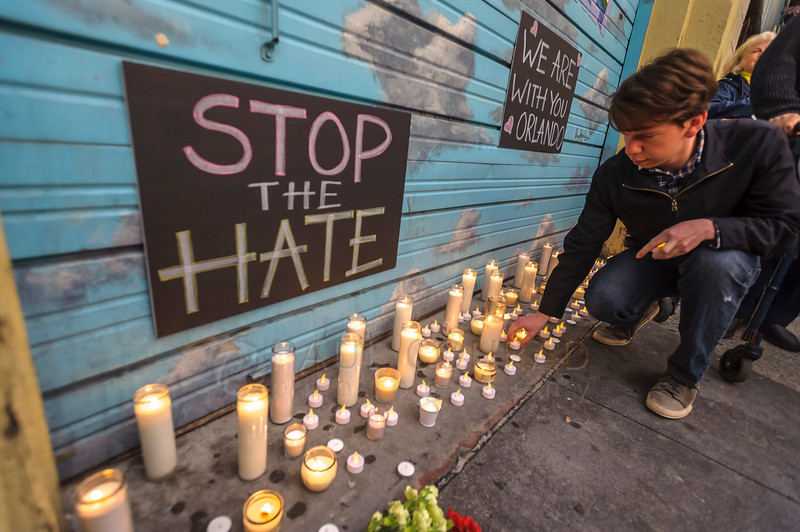 A man lights candles for a vigil for the victims of the Orlando, Fla., nightclub massacre on Monday evening June 13, 2016, at Rumors Cabaret in Bellingham, Wash. Over a hundred people turned out to honor those killed in the terrorist attack. Organizer Heidi O'Hana said she she was