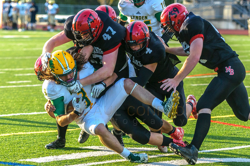 Lynden's Rylan Severson (3) is gang tackled by the Mount Baker defensive line during opening football jamboree on Saturday evening August 27, 2016, at Civic Stadium in Bellingham, Wash. Varsity and junior varsity high school teams from Lynden, Everett, Squalicum, and Mount Baker played to test their skills. (© Paul Conrad/The Bellingham Herald)