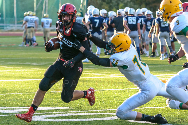 Jamboree - Mount Baker senior running back Jed Schleimer (4) evades Lynden junior defensive man Trey LaBounty (76) during a football jamboree on Saturday evening August 27, 2016, at Civic Stadium in Bellingham, Wash. (© Paul Conrad/The Bellingham Herald)
