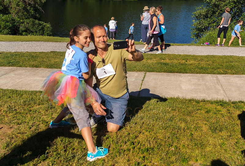 Mike Wylie of Blaine and daughter Olivia, 9, take a selfie before the start of the 2016 Girls On The Run 5K on Saturday morning June 4, 2016, at Lake Padden in Bellingham, Wash. GOTR director Jen Gallant said over 700 people registered for the fun run which included 400 participants in the GOTR and Trailblazer program as well as 300 adults from various YMCAs around the Puget Sound. She added GOTR is a YMCA after school program designed to encourage positive emotional, social, mental, spiritual and physical development. (© Paul Conrad/The Bellingham Herald)