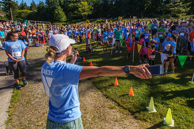 Girls on the Run Director Jen Gallant directs the over 700 participants to the start line of the 2016 Girls On The Run 5K on Saturday morning June 4, 2016, at Lake Padden in Bellingham, Wash. GOTR director Jen Gallant said over 700 people registered for the fun run which included 400 participants in the GOTR and Trailblazer program as well as 300 adults from various YMCAs around the Puget Sound. She added GOTR is a YMCA after school program designed to encourage positive emotional, social, mental, spiritual and physical development. (© Paul Conrad/The Bellingham Herald)