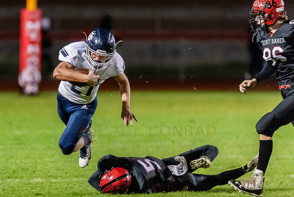 Lynden Christian def Mount Baker 27 to 8 - Lynden Christian running back Levi Korthuis (21) jumps over Mount Baker defensive back Ayden Rodriguez (5) as linebacker Waylon Kentner (86) moves in as he sweeps around the line of scrimmage during the second quarter on Friday evening Oct. 18, 2019, on Bob Tisdale Field at Mount Baker High School in Deming, Wash. Lynden Christian defeated Mount Baker 27 to 8. (photo © Paul Conrad /Paul Conrad Photography)