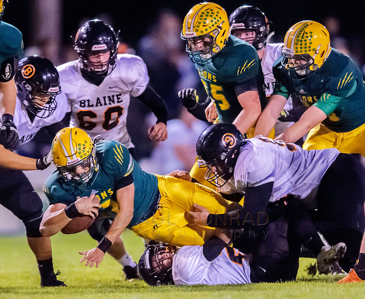 Crushed - Lynden's Jacob Hommes (2) gets spulled down by Blaine's Garrett Adams (29), bottom, at the line of scrimmage during the first quarter on Friday evening Oct. 7, 2016, at Lynden High School in Lynden, Wash. (photo © Paul Conrad/The Bellingham Herald)