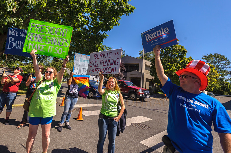 Christina Farsovitch, left, her daughter Elaina Farsovitch, both from Marysville, and Scott Sanderson of Bellingham, right with flag, cheer as the March for Bernie Rally begins on Saturday afternoon July 24, 2016, in downtown Bellingham, Wash. (© Paul Conrad/The Bellingham Herald)