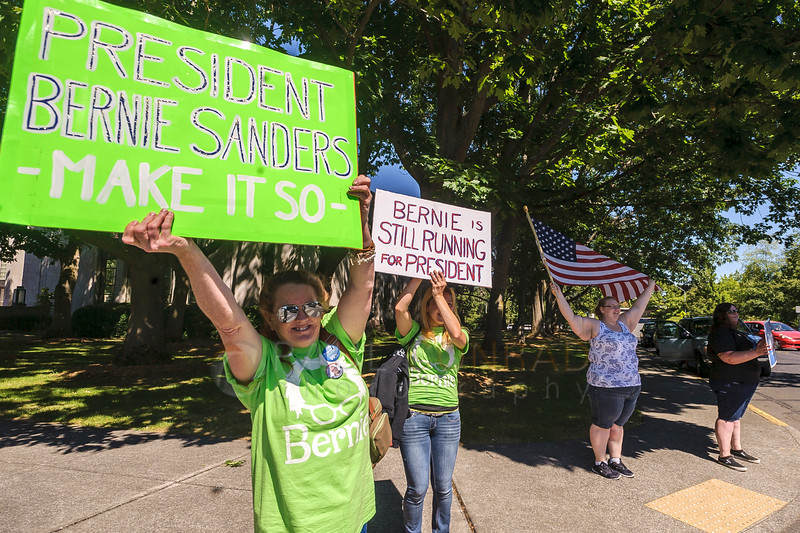 Christina Farsovitch, left, and her daughter Elaina Farsovitch, both from Marysville, cheer passing cars before the March for Bernie Rally on Saturday afternoon July 24, 2016, in downtown Bellingham, Wash. (© Paul Conrad/The Bellingham Herald)