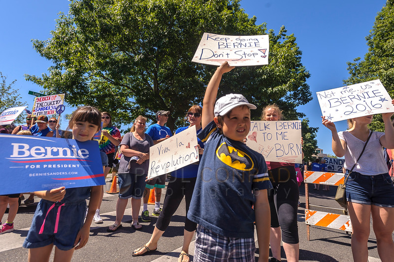 Logan Lundy, 7, of Bellingham cheers passing cars with other rally goers during the March for Bernie Rally. One question you must ask: Does a 7-year-old really know about politics?. (© Paul Conrad/The Bellingham Herald)