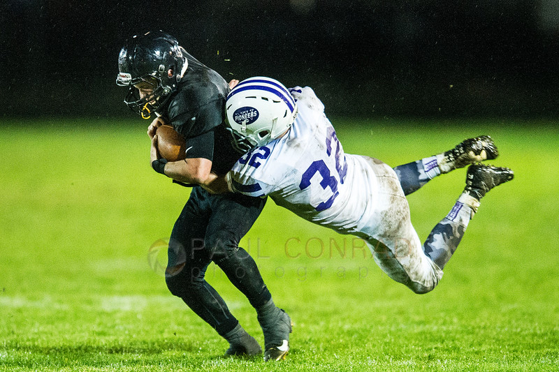 Flying Tackle - Meridian's Cole Roberts (5), left, gets stopped on a sweep at the line of scrimmage by Nooksack Valley's Mark Coppinger (32) early in the fourth quarter on Friday evening Oct. 21, 2016, at Meridian High School in Laurel, Wash. (© Paul Conrad/The Bellingham Herald)