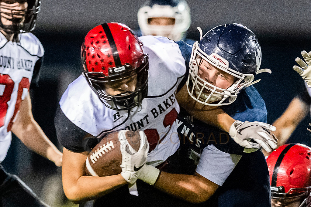 Mount Baker vs Lynden Christian - Mount Baker running back Jason Lee (31), left, gets pulled down by Lynden Christian linebacker Dylan Kaemingk (55) after a short gain during the first quarter on Friday evening Oct. 12, 2018, at Lynden Christian High School in Lynden, Wash. The visiting Mount Baker defeated Lynden Christian 20 to 14. (Paul Conrad for the Bellingham Herald)