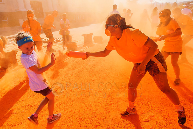 "In Your Face! - Volunteer Nina Poliquit of Olympia sprays participants with orange powder during The Color Run on Sunday morning Aug. 21, 2016, in downtown Bellingham, Wash. Several thousand participated in the ""World's Happiest 5K"" fundraiser to help benefit the Whatcom Family YMCA. (© Paul Conrad/The Bellingham Herald)"