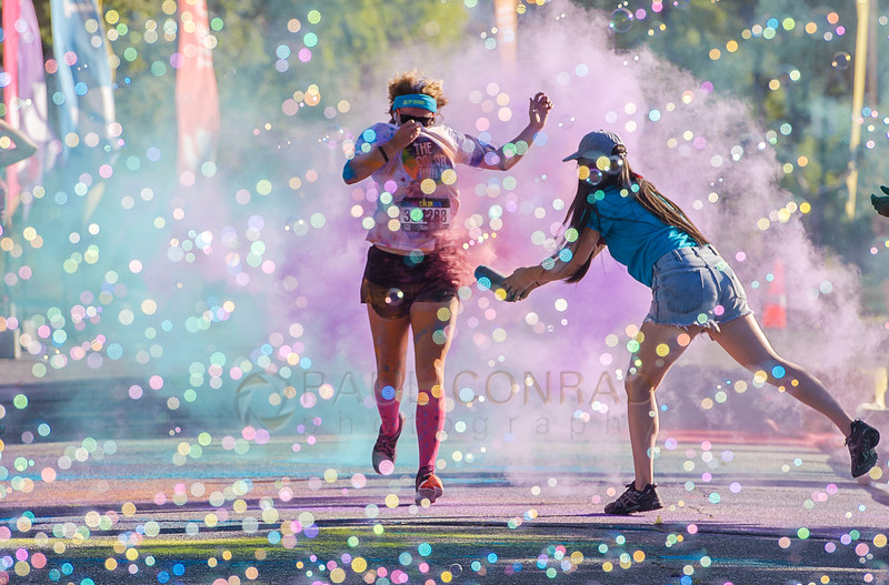 A volunteer sprays a participant with colored powder during The Color Run on Sunday morning Aug. 21, 2016, in downtown Bellingham, Wash. Several thousand participated in the