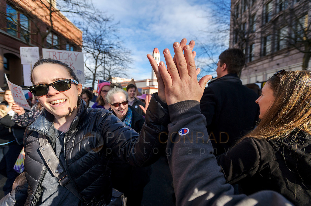 High Fives for Rights - A pair of demonstrators give a high-five as thousands march through downtown Bellingham, Wash., during the Women's March on Bellingham on Saturday Jan. 21, 2017. (© Paul Conrad/The Bellingham Herald)