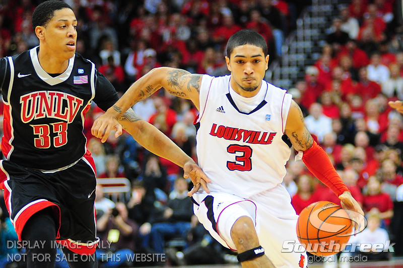 Louisville Cardinals guard Peyton Siva (3) drives past UNLV Rebels guard Tre'Von Willis (33).  Louisville Cardinals defeated UNLV Rebels 77 - 69 at the KFC Yum Center in Louisville, Kentucky.