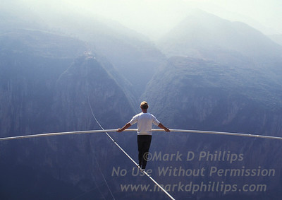"""Jay Cochrane, """"The Prince of the Air"""", practices for his skywalk over the Yangtze River in Qutang Gorge, China, in 1995. The skywalk was and is the greatest ever made spanning half a mile between the canyon walls and 1,350 feet above the river.  ©/Mark D. Phillips"""
