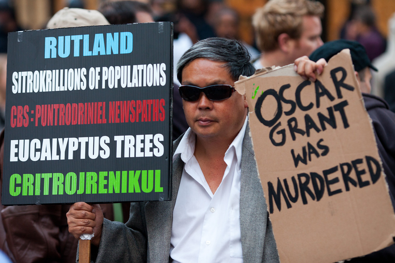 Frank Chu Holds Signs, Oakland Riots, 2010
