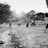 Hmong children playing a ball game of their own as the sun goes down on their mountain village in northern Thailand<br /> <br /> Play Ball<br /> Kun Chang Kian Hmong Village, Chiang Mai Region, Thailand