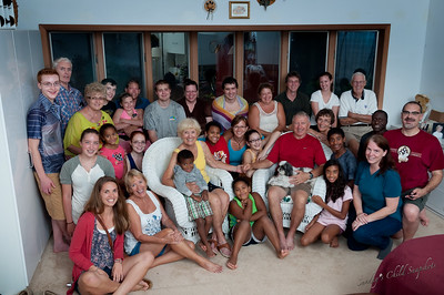 Sunday September 2, 2012  Family  This is from the family reunion in New York this summer. I think it would have been fun to try to pose everybody in a creative way. But it was task enough to get everybody in one spot large enough for the whole group. We would have done it outside, but it was raining.  [edit by david] Because of some remote control issues with Nikon's CLS in large spaces or long distances, I'd purchased two sets of Yongnuo RF-603 remotes. These have short cables that can plug into a camera and remotely fire the shutter. For this shot, the camera was on a tripod with one of the remotes on top.  There were two umbrellas, one on each side side of the camera, remoted by the Yonguo's.  And in the back, behind the camera, was another flash (optically slaved) on top of a bookshelf aimed at the cathedral ceiling.  The fourth remote was in my hand so I could take the picture (Doh! I just noticed that you can see it - the light is red because the shutter was open.)  I've not used the remotes too much yet, but so far, they've worked well.  In fact, the other night, I pulled a pair out so Jacci could take the moon shots without disturbing the camera on the triopd.  (Using the self time for those shots, even at two sections is a pain...)  I think eventually I want to get at least another pair.