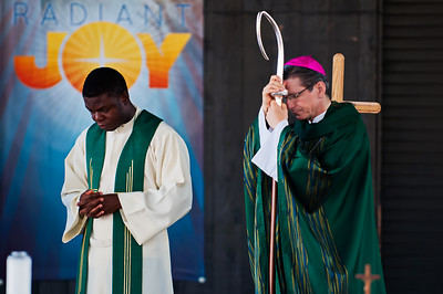 "Tuesday August 14, 2012  Radiant Joy  This is Archbishop Gustavo Garcia-Siller of San Antonio and Fr. John. I wish I could tell you Fr. John's full name. He made a guest appearance Saturday at Mass and I did not understand the full pronunciation of his name when he was introduced. I believe he is from someplace in Africa. When he spoke, he had a gorgeous accent, full of both culture and compassion. The Archbishop is originally from Mexico. I met him earlier this year when he sat a few seats from David and me at the screening of ""For Greater Glory"". What a beautiful soul he is, so gentle and joyful, despite the many atrocities he has witnessed in his life. I took this shot during the Gospel proclamation. When I was going through the pictures from Saturday, this one caught my eye because of Fr. John and the banner behind him. It's why I took the shot. But on my computer, the radiance is even stronger than it was in my camera."