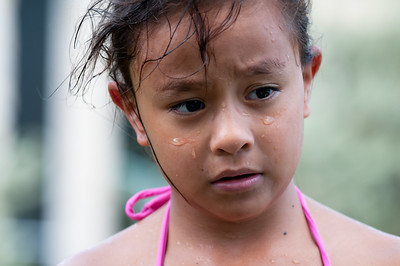 Thursday August 30, 2012  The Crushed in Spirit  This was just a simple snapshot. Jasmine had just gotten out of the pool and dropped her goggles to the ground, annoyed because Julia and Jeanette had teamed up against her. The three of them are identical triplets and absolutely love being together, but sometimes, there are hurt feelings when somebody feels left out. This shot melted my heart because of the way her eyebrows tell the story of her hurt feelings. I also kind of like the way the mark from the goggles is still visible at the bridge of her nose. Poor Jasmine. Don't worry, though... Her beautiful smile returned when the pizza came out a few minutes later.