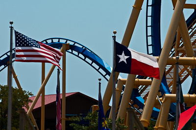Monday August 13, 2012  Two Flags at Six-Flags  My friend, Morag and I were in the water park part of the amusement park when I noticed the picture perfect view of the flags at the entrance. It took some patience to wait for just these two flags to wave while the others rested. I wanted to get a shot with a car of screaming people on rails AND the two flags. But I could have spent the whole day waiting for that shot since there really wasn't much wind. I decided against waiting for the perfect storm. I'll take my two flags at Six-Flags.