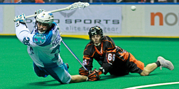 The Rochester Knighthawks secure a playoff berth on the last game of the regular season in a 10-9 win over the Buffalo Bandits.  Rochester's Stephen Keogh lands a behind the back shot on goal in the final minute while being dragged to the turf by Buffalo's Alex Kedoh Hill.  April 20, 2013, First Niagara Center, Buffalo, NY.