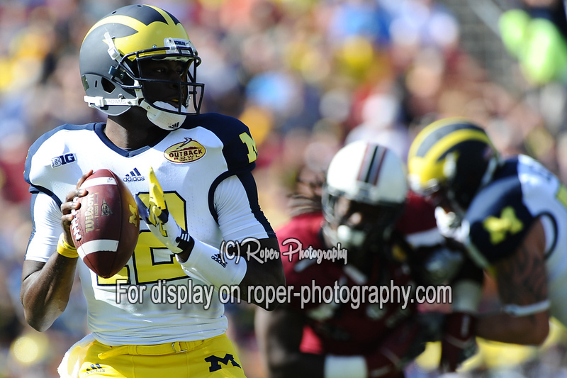 Michigan Wolverines quarterback DEVIN GARDNEER (12) looks for an open receiver while South Carolina Gamecocks defensive end JADEVEON CLOWNEY (7) pressure him in the first half of the 2012 NCAA Outback Bowl between the South Carolina Gamecocks and the Michigan Wolverines at Raymond James Stadium.
