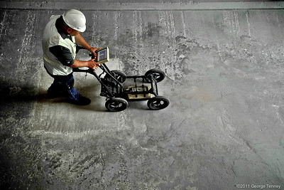 Technician using ground penetrating radar floor scanner