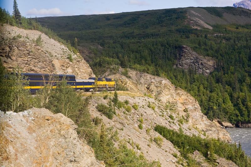 Alaskan Railroad train running alongside the Nenana River in Alaska.
